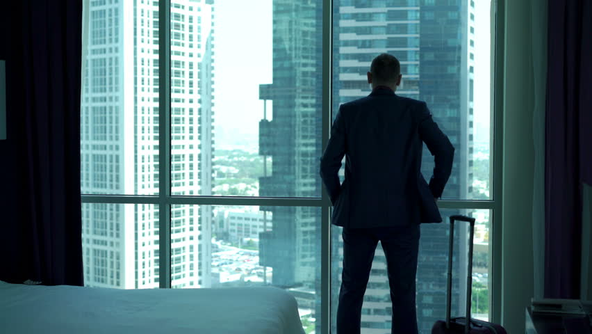 Young businessman enter the hotel room with splendid view and looking through the window, 4K  | Shutterstock HD Video #21064216