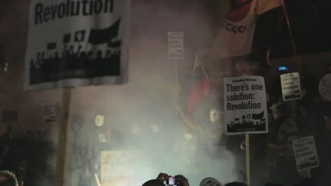 LONDON, UK - NOVEMBER 5, 2016: Protesters and Anonymous supporters wearing Guy Fawkes masks lit up Trafalgar Square in London with flares as part of the annual anti-capitalist Million Mask March.
