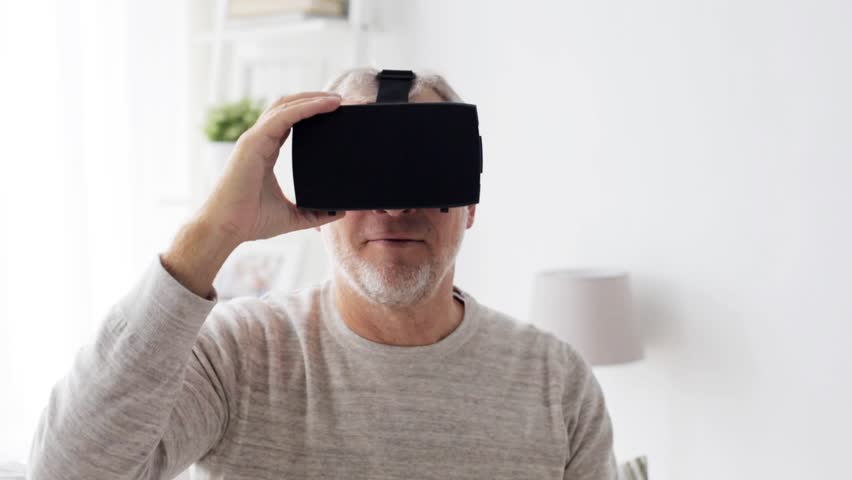3d technology, augmented reality, gaming, entertainment and people concept - senior man with virtual headset or 3d glasses playing videogame at home