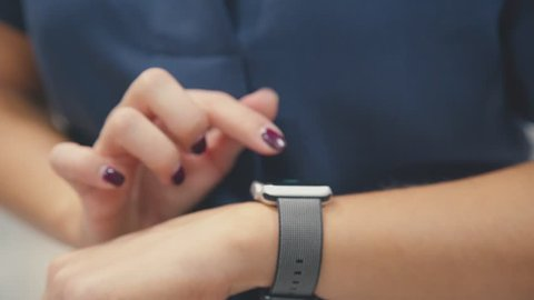 b53c1a6a8e Woman using her smartwatch touchscreen wearable technology device. Young  woman trying new smart watch.