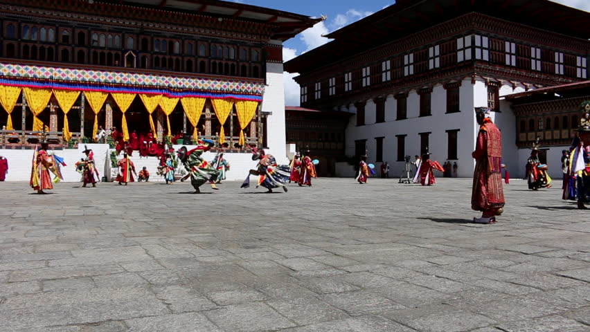 Bhutan Festival with dancers in costumes in a monastery