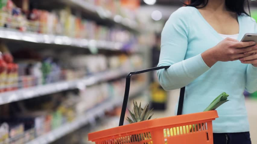 Shopping, technology, sale, consumerism and people concept - woman with smartphone and food basket at supermarket or store | Shutterstock HD Video #21124231
