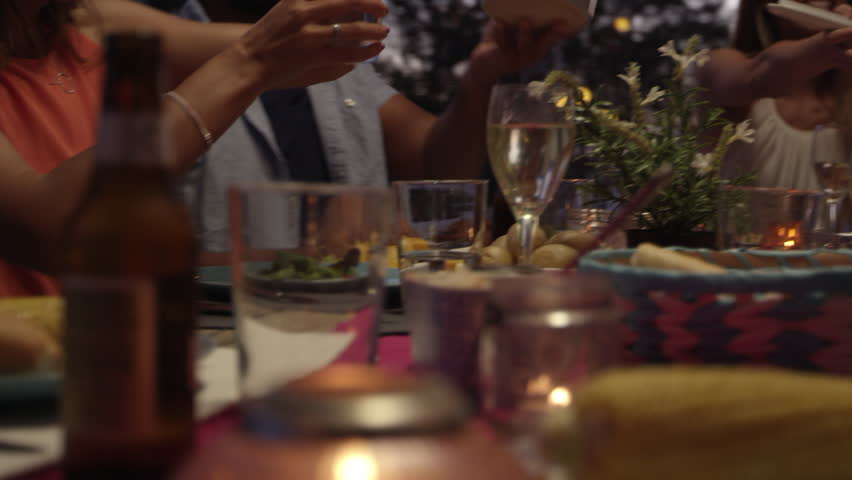 Friends passing food at dinner on a roof terrace, close up, shot on R3D