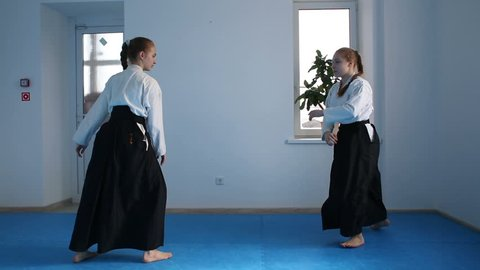 Two girls in black hakama practice Aikido