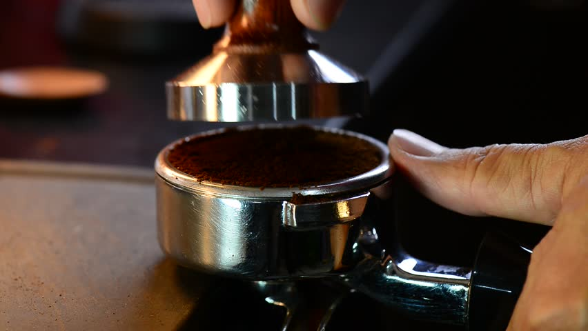 Barista is preparing ground for double shot of espresso   ,coffee concept.Coffee tamper.