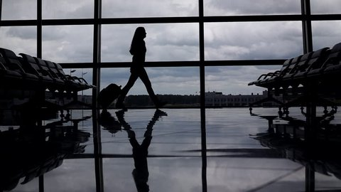 Traveller woman go against lounge window with trolley case, slow motion. Silhouette view, air transportation concept. Empty airport terminal airside area. Self reliant lady proceed to boarding gate