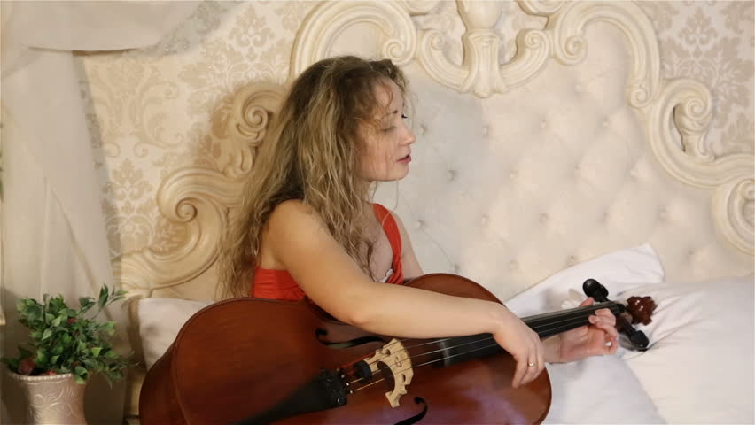 Impressive attractive fashion model with long hair, a photoshoot on the bed with a cello. | Shutterstock HD Video #21171196