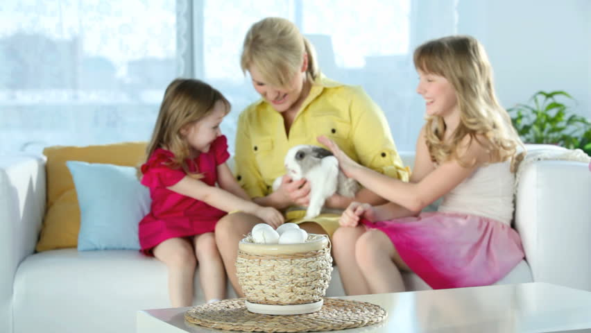 Family spending time at home, mother holding an adorable bunny while daughters caressing it, Easter series