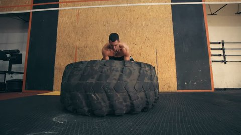 Strong muscular young man flipping tyre while exercising in CrossFit gym.