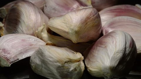 Garlic cloves vegetables food gyrating on black background