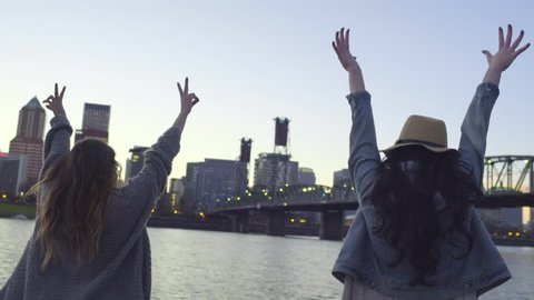 Young Women Raise Their Arms In Air Hold Peace Signs, Backs To Camera
