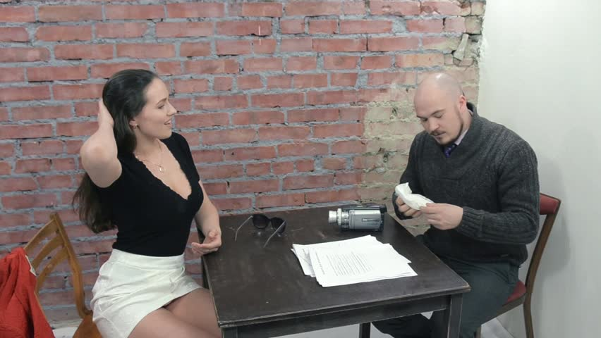 Man sit at table and interviewing young woman in mini skirt, which touch hair. Decollete. Casting. Camera on table. Brick wall on background