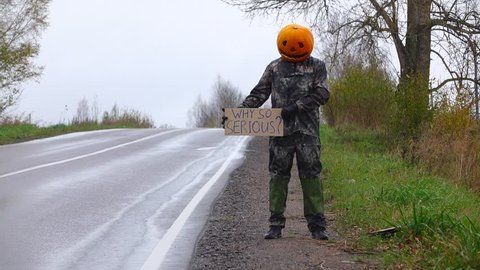 Man perform odd prank, stand with carton sign at roadside, ask why so serious. Empty rural road and rainy weather, freak guy wear halloween pumpkin on head. No cars drive, he put down cardboard plate