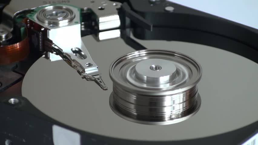 Metal circle plate and magnetic head inside hard disk drive reading and writing data   Shutterstock HD Video #21255604