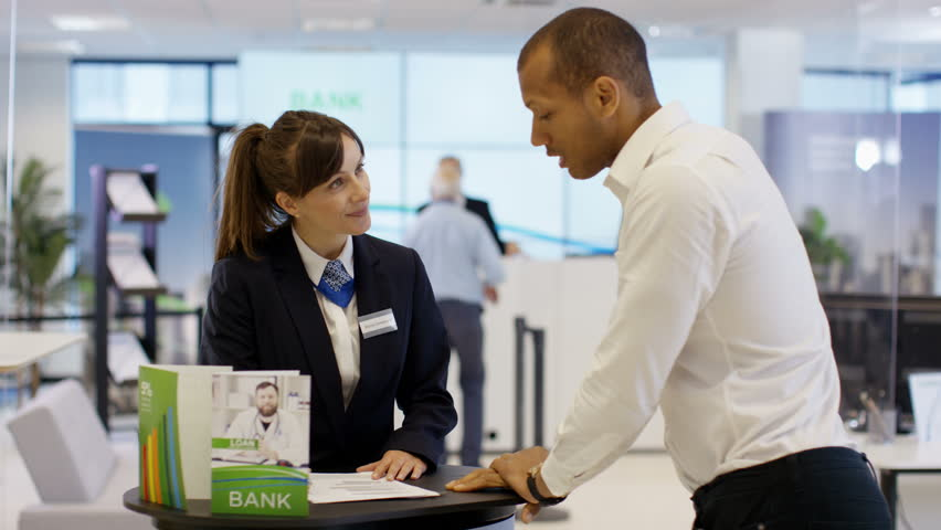 4K Bank worker on information desk giving help & advice to customers. Shot on RED Epic. | Shutterstock HD Video #21274612