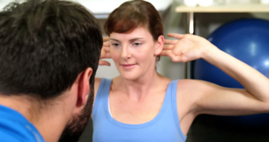 a college professor helps students understand a chemistry  male physiotherapist assisting a female patient while exercising in the clinic 4k 4k stock footage