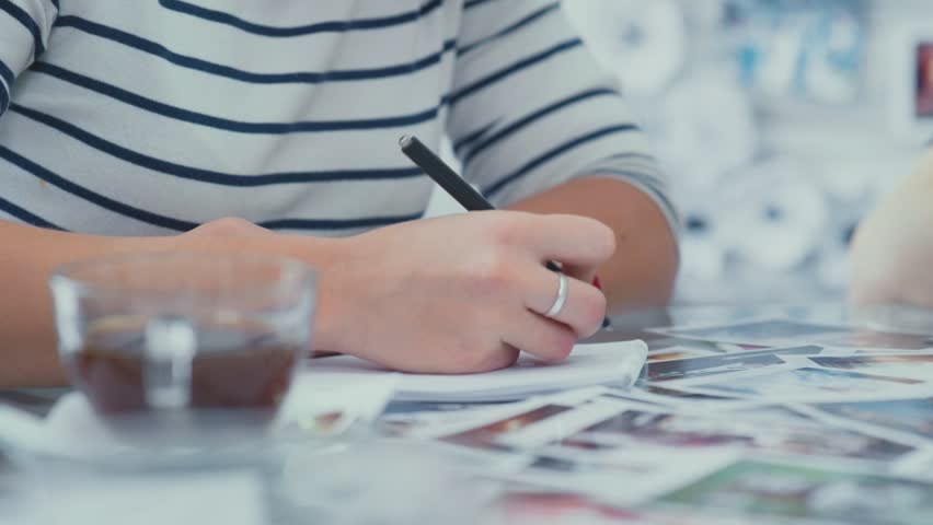 Close-up of a woman writing in a notebook. Notepads on the table. business attributes. A woman in a striped jacket taking notes in a notebook during a business meeting. Sketchbooks. | Shutterstock HD Video #21310096