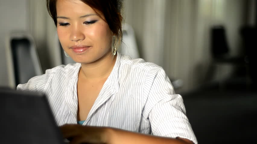 Young Asian woman smiles while typing on a laptop.