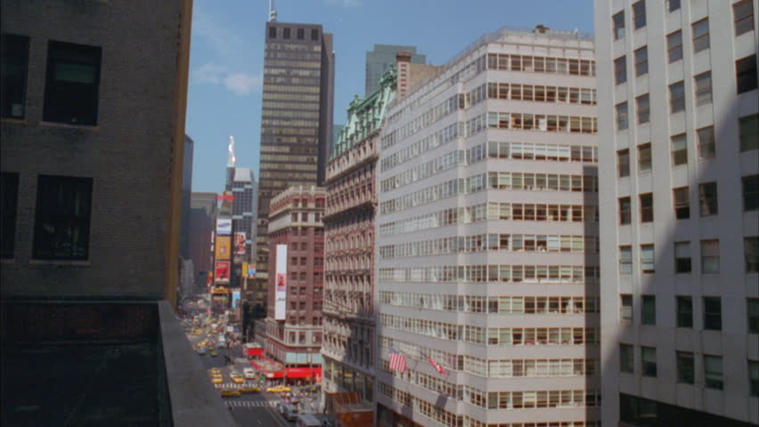 city building side. day High angle down Times Square city street area background then Pan right  side Raked Day Angle Right Over City Buildings Tight Side
