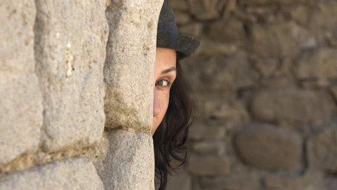 Beautiful girl in a hat peeking behind the wall and smiling