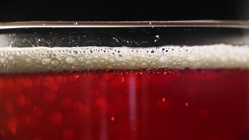 A close profile shot of a glass of red beer. | Shutterstock HD Video #2134046