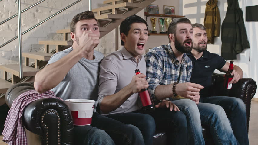 Lockdown best friends sitting on sofa enjoying beer and watching match on TV, then celebrating goal and screaming in happiness | Shutterstock HD Video #21345196