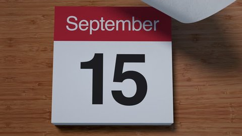 Calendar for September on wooden table flipping through days of month