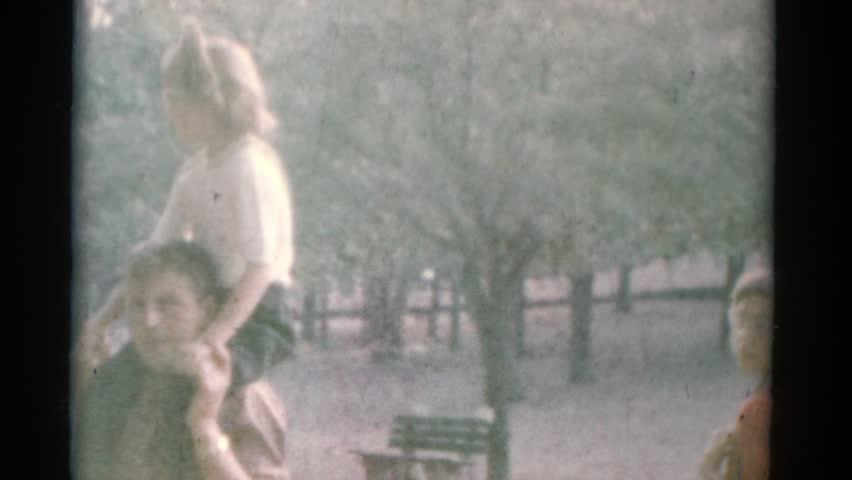 CATSKILL, NEW YORK 1962: small girl riding on man's shoulders near zoo exhibit #21374086
