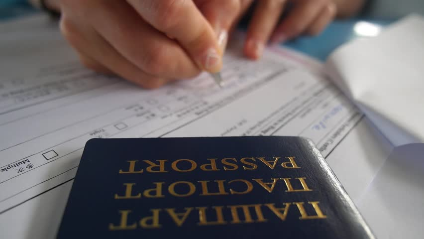 Closeup Hands Filling in Application Form for Visa Entry