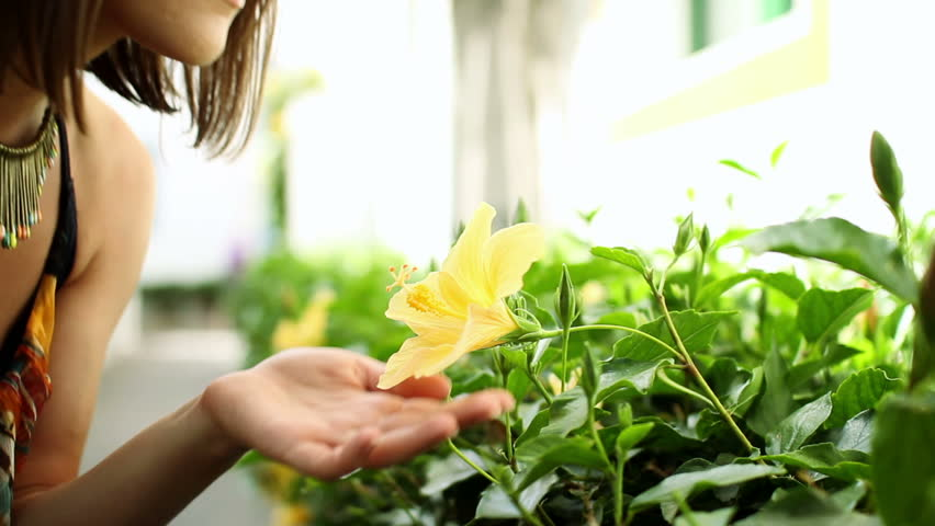 Young happy woman smelling yellow flower