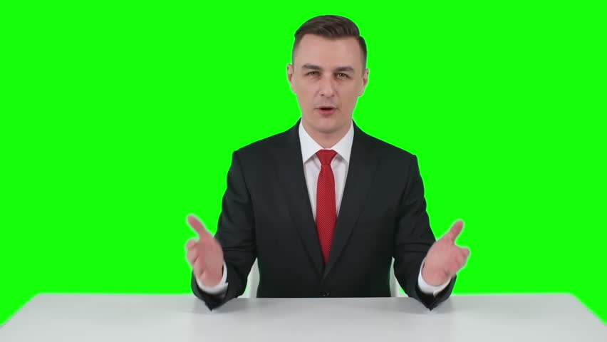 Man in suit sitting behind table gesticulating and showing something with his hands, green screen backdrop in background  | Shutterstock HD Video #21385126