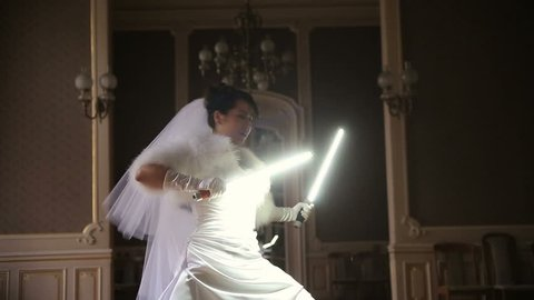 Funny pretty bride playing jedi with lightsaber. Unusual wedding ceremony