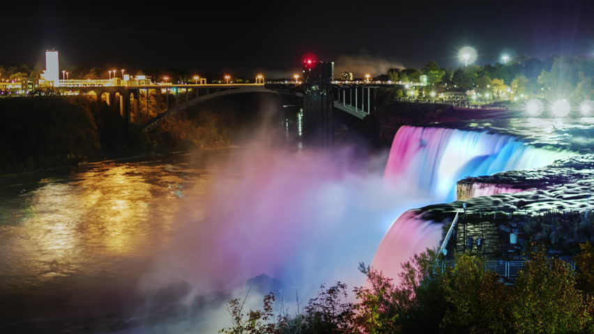 Night Show Niagara Falls. Tourists on a viewing platform to admire the illuminated waterfall