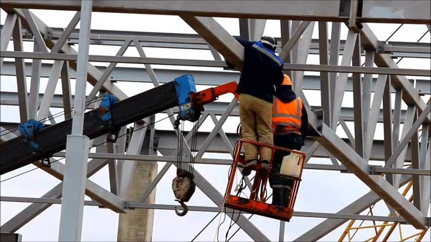 A welder working at height without insurance in a cradle lift in the construction of large shopping complex metal structures and concrete piles. safety rules violation | Shutterstock HD Video #21447046
