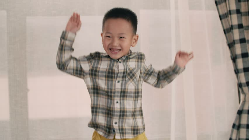 The little boy of Asian appearance, having fun on the sofa in the room, jumping in slow motion | Shutterstock HD Video #21451126