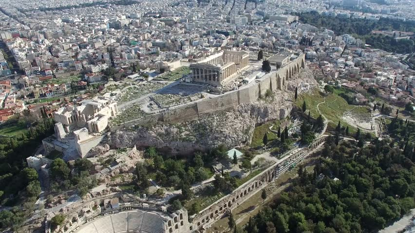 Aerial flying around the Acropolis of Athens ancient citadel located on rocky outcrop showing Parthenon very famous tourist attraction in Europe Greece European visit furthermore showing downtown 4k