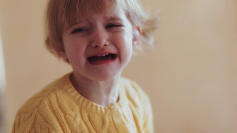 A little cute blonde baby-girl in a yellow warm sweater in the home interior surroundings crying loudly. Angry little girl with sad expression, screaming and crying. Close up view.
