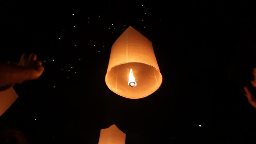 people launching traditional fire lantern during Loi Krathong festival in Chiang Mai, Thailand