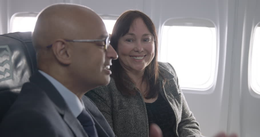 Asian business man and smartly dressed Caucasian woman talking and smiling as they sit in first class section of commercial airliner.  Medium close up with camera dolly and focus on female passenger.
