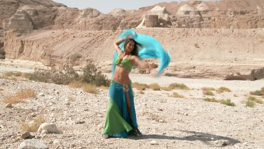 Female dancer. Muslims belly dance. Belly dance sequence. Beautiful , happy belly dancer dancing ethnic dances in a desert. In sexy green blue dress dancing .
