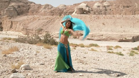 Female dancer. Muslims belly dance. Belly dance sequence. Beautiful , happy belly dancer dancing ethnic dances in a desert. In sexy green blue dress dancing .