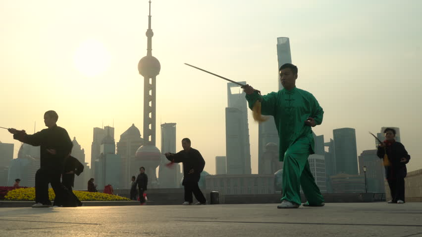 Shanghai, China - March 2016: Group exercising with Tai Chi on The Bund