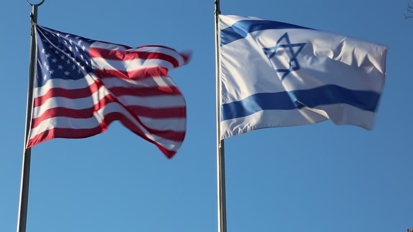 Large American and Israeli flags waving together on a windy day