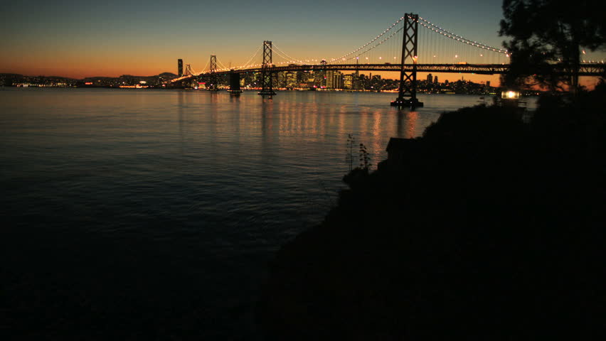 Aerial sunset time lapse view of the Oakland Bay bridge, Fishermans Wharf and the city skyscrapers of San Francisco,