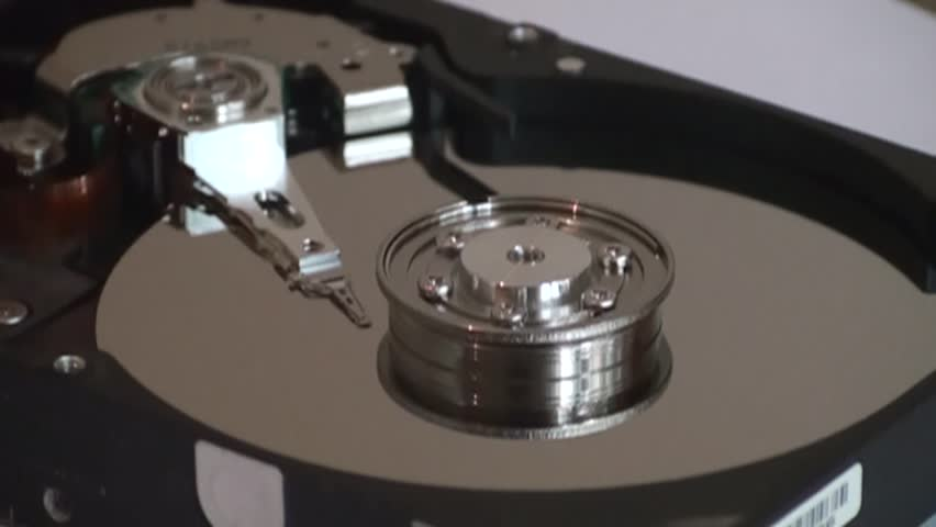 Metal circle plate and magnetic head inside hard disk drive reading and writing data   Shutterstock HD Video #21495778