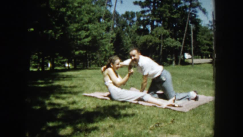 WISCONSIN 1953: a couple playfully snuggles and hugs on a picnic blanket in the grass.