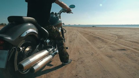 Motorcyclist riding along the sandy beach. Biker rides a motorcycle through the desert. Drift on a motorcycle. Vehicle acceleration skid on sand. Chopper near the shore of the river, sea, lake, ocean.