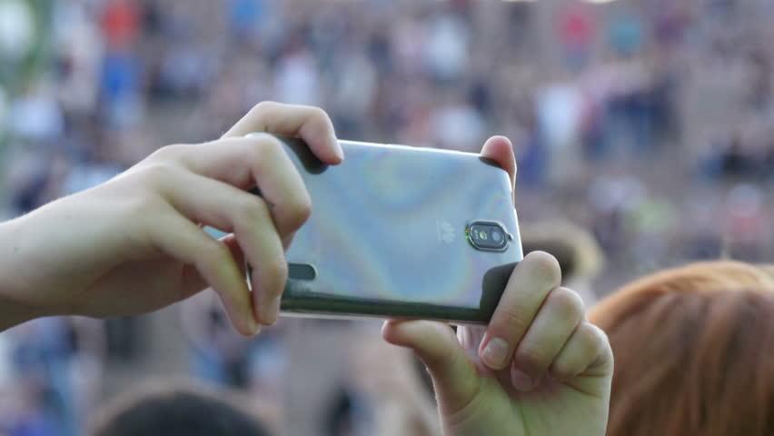 Kiev, Ukraine - August 24, 2016: woman recording video on the free concert