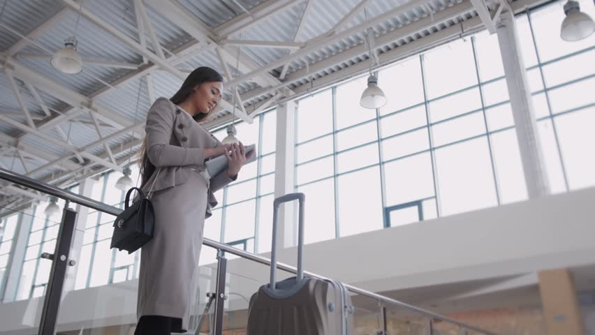 Beautiful young woman using tablet computer at airport. Elegant businesswoman in terminal with suitcase waiting plane | Shutterstock HD Video #21536566