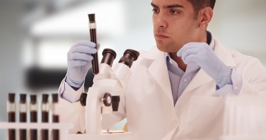 Millennial Hispanic medical scientist in laboratory looking through microscope. Latino research technician using blood samples in test tubes. 4k | Shutterstock HD Video #21541576